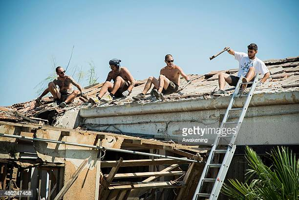 Volunteers from 'Centri Sociali Nord Est' check one of the roofs damaged two days ago by the tornado on July 10 2015 in Venice Italy One person died...
