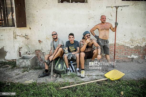 Volunteers from 'Centri Sociali Nord Est' take a break while clearing the damage caused by the tornado on July 10 2015 in Venice Italy One person...