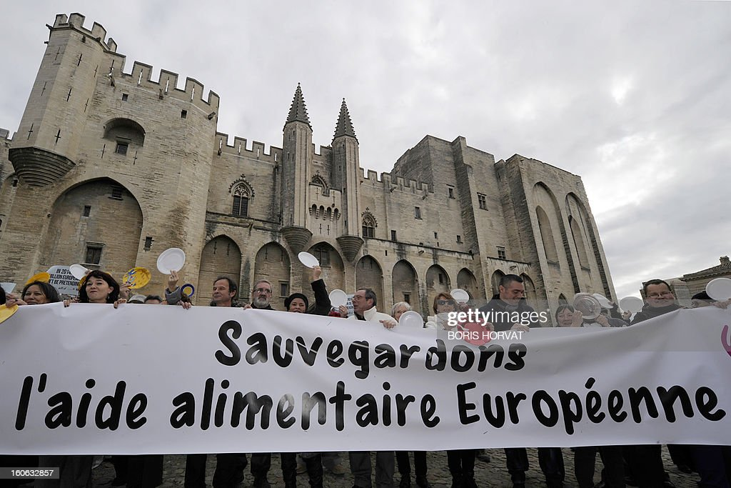 Volunteers from food aid associations such as Banques Alimentaires, Croix-Rouge, Restos du Coeur and Secours Populaire, hold a banner reading in French 'Save european food aid' on February 4, 2013 in Avignon, south of France, as part of a nation wide day asking for more European subventions.