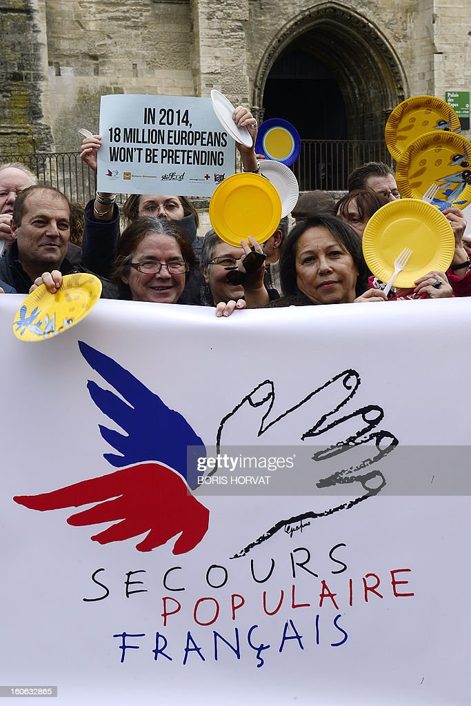 Volunteers from food aid associations such as Banques Alimentaires, Croix-Rouge, Restos du Coeur and Secours Populaire, hold a banner on February 4, 2013 in Avignon, south of France, as part of a nation wide day asking for more European subventions.