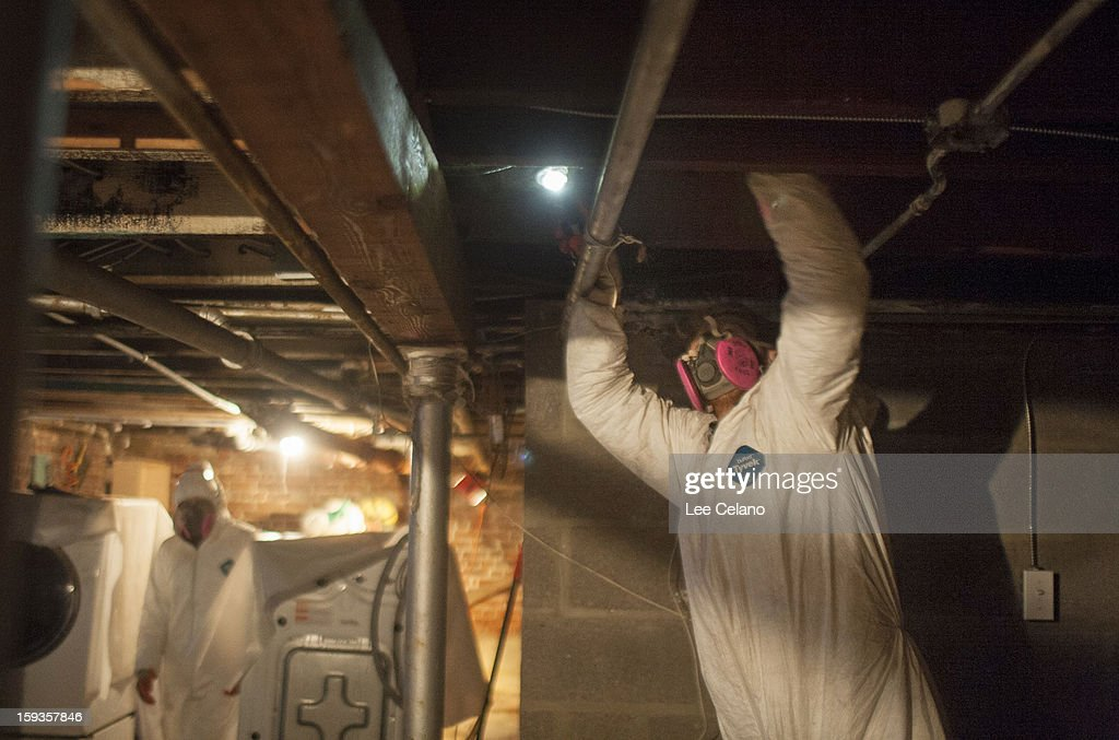 Volunteers from from the Respond and Rebuild group remove mold from a house damaged in Hurricane Sandy January 12, 2013 in the Rockaway neighborhood, of the Queens borough of New York City. Congress will vote on an aid bill for hurricane victims January 15.
