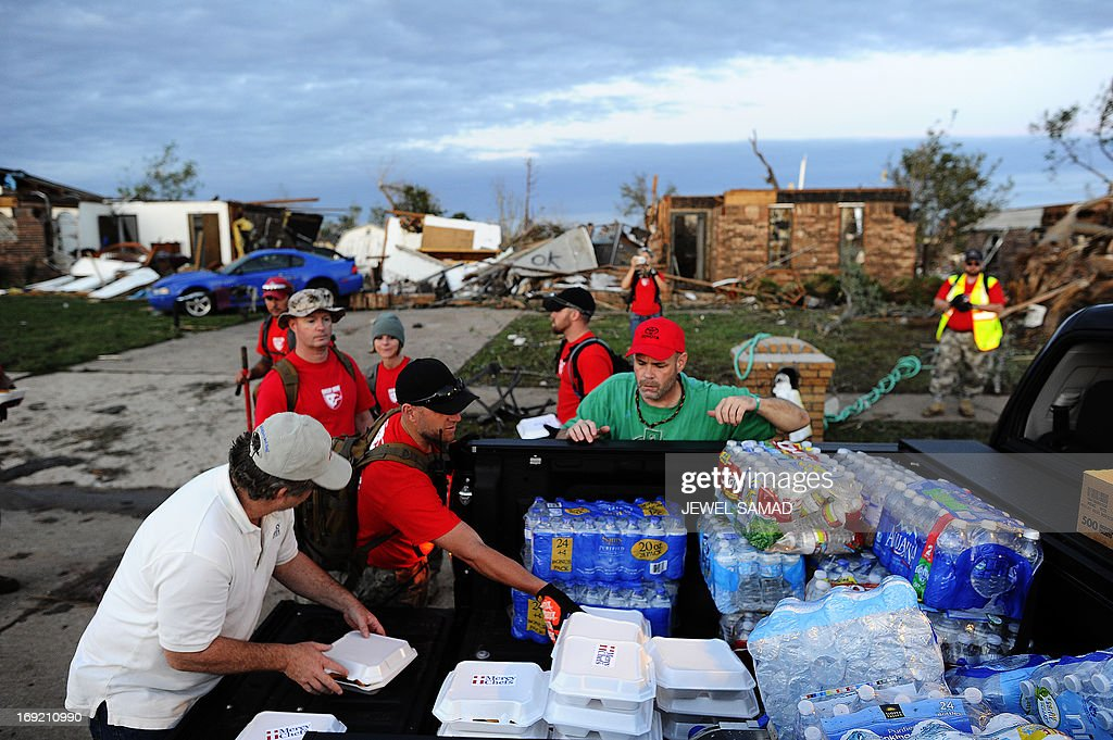 Volunteers from Mercy Chefs distribute hot food to tornado victims and rescue workers at a devastated neighbourhood on May 21, 2013 in Moore, Oklahoma. Families returned to a blasted moonscape that had been an American suburb Tuesday after a monstrous tornado tore through the outskirts of Oklahoma City, killing at least 24 people. Nine children were among the dead and entire neighborhoods vanished, with often the foundations being the only thing left of what used to be houses and cars tossed like toys and heaped in big piles. AFP PHOTO/Jewel Samad