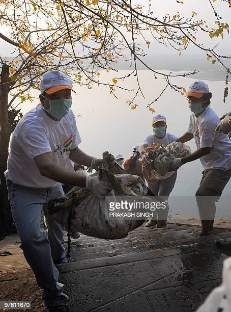 Volunteers from The Art of Living Foundation clean the ghats of polluted Yamuna river during a cleansing drive in New Delhi on March 18 2010...