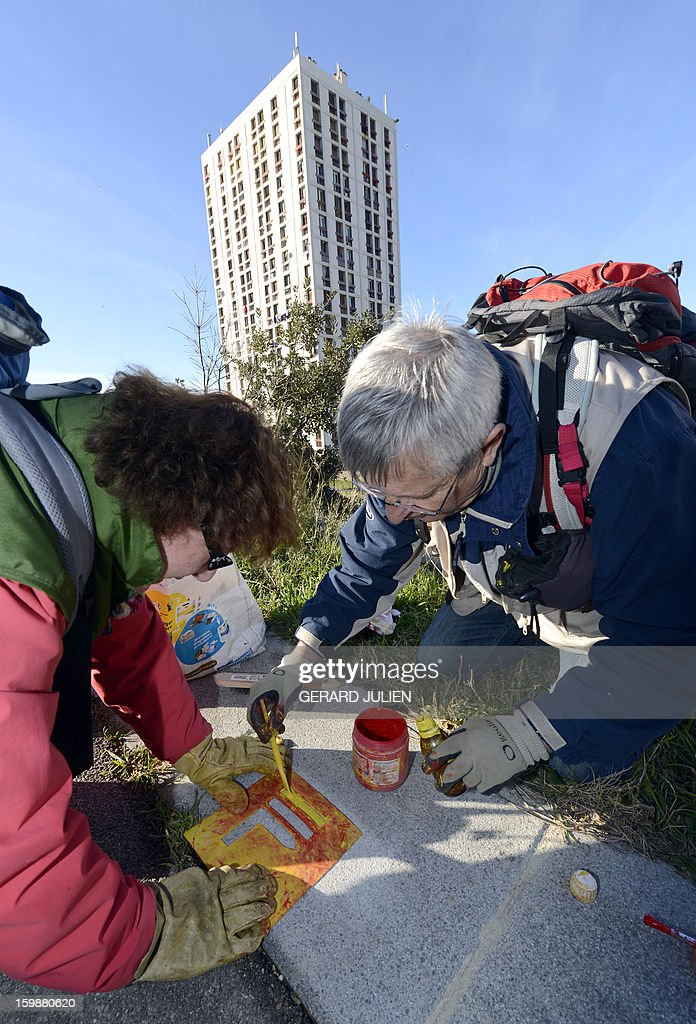 Volunteers from the 'Fédération Française de Randonnée Pédestre' (FFRP - French Federation of Pedestrian Hiking) mark the path of the GR2013 hiking route with red and yellow paint, in Marseille, on January 22, 2013. The GR2013 hiking route was established as part of the 'Marseille-Provence European Capital of Culture 2013' program, which sees Marseille host a variety of cultural activities throughout the year. The GR2013 path is 360kms long and crosses through both urban and natural areas, forming an infinity symbol and loop. The GR2013 will be ready and open to the public as of March 22. AFP PHOTO / GERARD JULIEN