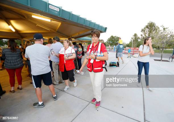 Volunteers from the Red Cross hand out bottles of water during a prayer vigil held at Mountain Crest Park for the victims of Sunday night's shooting...