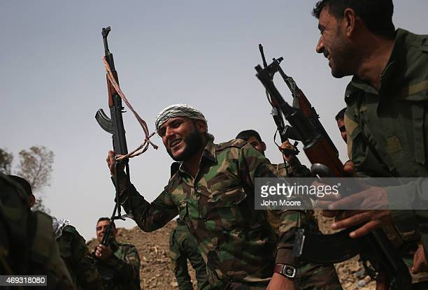 Volunteers from the Shia Badr Brigade cheer after an exchange of fire with ISIS fighters on the frontline on April 11 2015 in Ebrahim Ben Ali in...