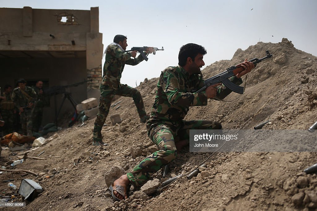 Volunteers from the Shia Badr Brigade militia fire on ISIS fighters on the frontline on April 11 2015 in Ebrahim Ben Ali in Anbar Province Iraq Shia...