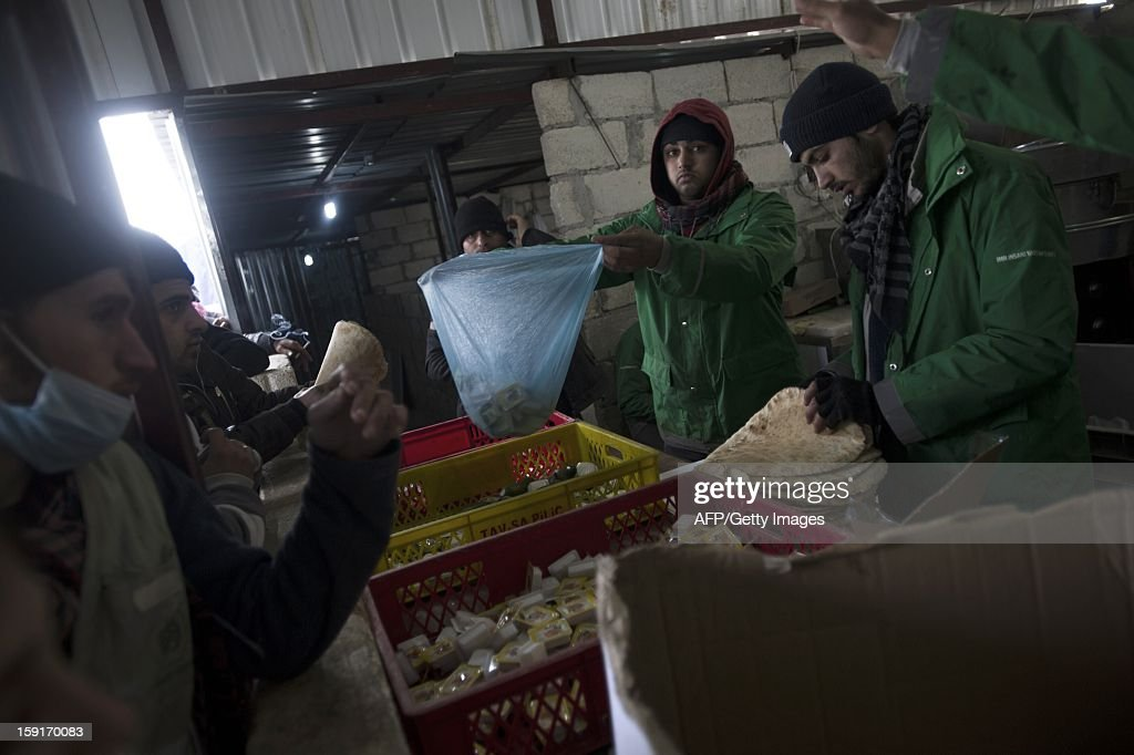 Volunteers from the Turkish Red Crescent hand out daily rations to Syian refugees at a camp for displaced people in Bab al-Salama on the Syria-Turkey border, on January 9, 2013. The internally displaced Syrians faced further misery due to increasing shortage of supplies as heavy rain was followed by a drop in temperatures. AFP PHOTO/ZAC BAILLIE