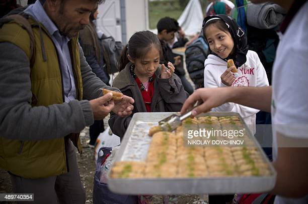 Volunteers give ''baklava'' a traditional sweet to migrants and refugees as they mark the EidalAdha festival at a register camp close to the...