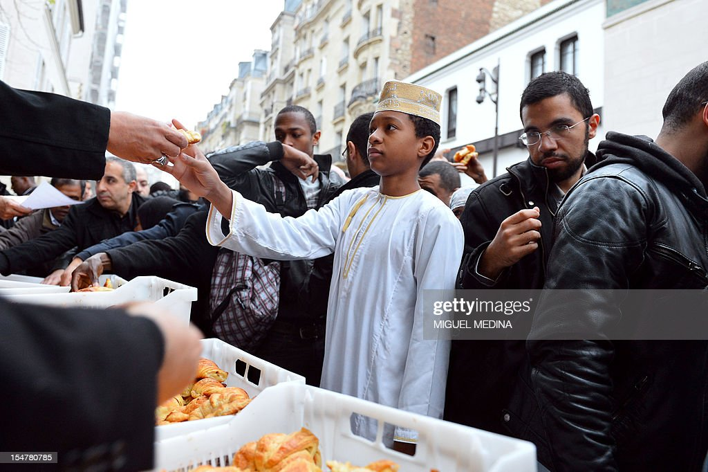 Volunteers give croissants 'Cope' to people after the Friday prayer outside the Grande Mosque of Paris on the first day of Eid al-Adha on October 26, 2012 in Paris. The croissants 'Cope' are given to protest against the October 5 remarks made by the general secretary of the rightist French Union for a Popular Movement (UMP) party, Jean-Francois Cope, to UMP supporters in Draguignan about a boy who allegedly had his 'pain au chocolat' (French pastries) stolen by 'thugs' during the fasting month of Ramadan. Eid al-Adha, or 'Feast of sacrifice' is celebrated throughout the Muslim world as a commemoration of Abraham's willingness to sacrifice his son for God, with cows, camels, goats and sheep traditionally slaughtered on the holiest day. AFP PHOTO MIGUEL MEDINA