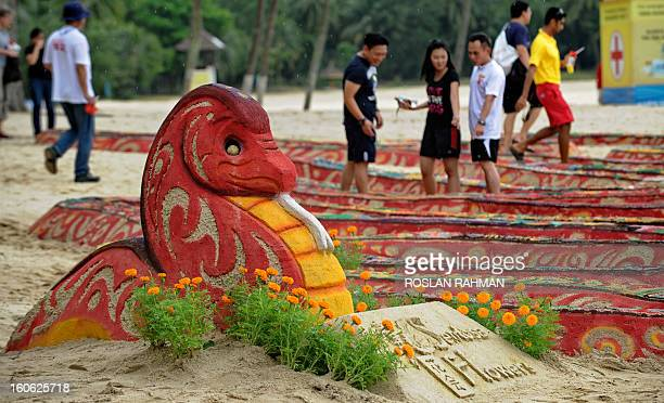 Volunteers give the finishing touches to a snake sand sculpture exhibited at the first sandy spring floral festival on Sentosa Island's Palawan beach...