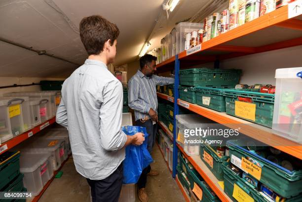 Volunteers Guilhem Chevallereau and Dhiren sort through food donations from the public at Oasis Foodbank Waterloo in London United Kingdom on May 16...