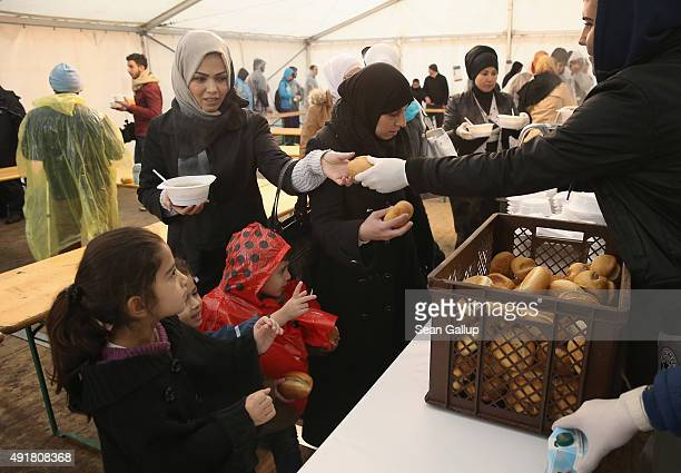 Volunteers hand out bowls of hot pasta in a tent to migrants who were waiting outside the Central Registration Office for Asylum Seekers of the State...