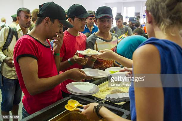 Volunteers hand over food to migrants who had arrived at Munich Hauptbahnhof main railway station on September 1 2015 in Munich Germany Over a...