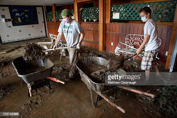 Volunteers Hank Sweeney and TJ McCarty clean up mud at The Crafts Inn on West Main Street where Tropical Storm Irene caused severe flooding in the...