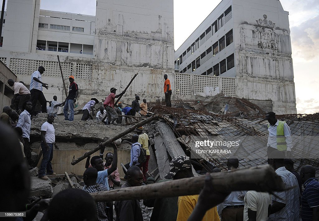 Volunteers help carry away debris from the scene of a collapsed building, on January 16, 2013 at Kenya's lakeside town of Kisumu. The building that was still under construction is suspected to have caved in on itself due to the failure of the site's contractors to adhere to appropriate standards of construction. AFP PHOTO/Tony KARUMBA