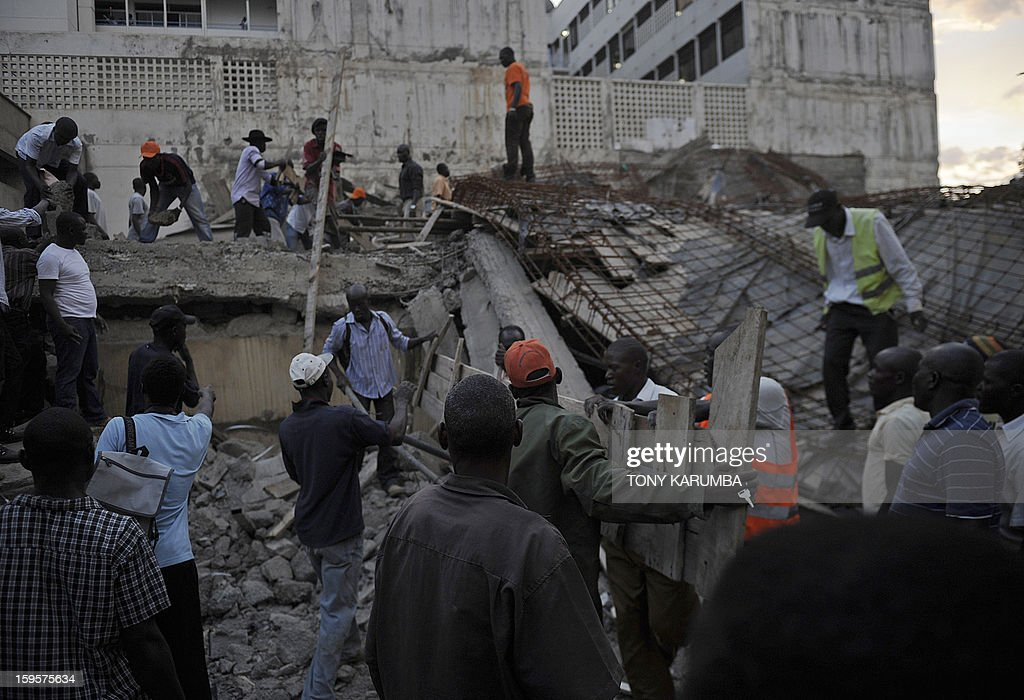 Volunteers help carry away debris from the scene of a collapsed building on January 16, 2013 at Kenya's lakeside town of Kisumu. The building that was still under construction is suspected to have caved in on itself due to the failure of the site's contractors to adhere to appropriate standards of construction. AFP PHOTO/Tony KARUMBA