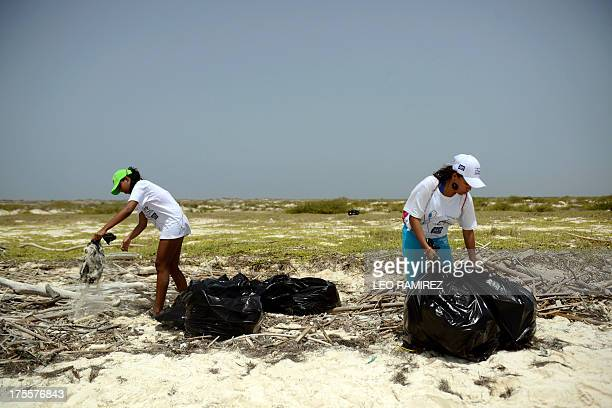 Volunteers help in the cleaning of La Tortuga Island in the southeastern Caribbean Sea Venezuela on August 4 2013 The government suspended by 30 days...