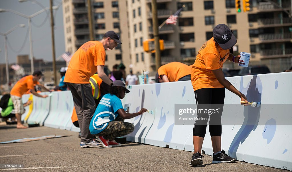 Volunteers help paint a mural along a roadway barrier on July 17, 2013 in the Rockaway neighborhood of the Queens borough of New York City. The project, which was put together by New York City Parks, invited artists to submit visions for how to reimagine ordinary objects in an effort to re-vamp the Superstorm Sandy damaged neighborhood; three final artists were chosen.