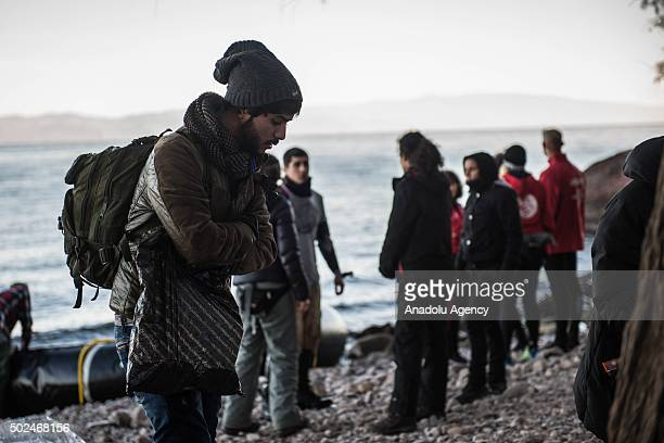 Volunteers help refugees upon their arrival on the shore of Lesbos Island Greece after crossing the Aegean sea from Turkey on December 24 2015