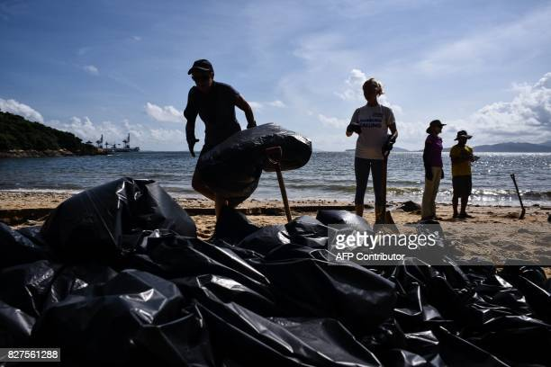 Volunteers help remove washed up palm oil from a beach in front of a pile of black bin bags on Hong Kong's outlying Lamma Island on August 8 2017...