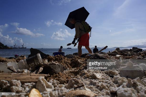 Volunteers help remove washed up palm oil from a beach on Hong Kong's outlying Lamma Island on August 8 2017 Residents in Hong Kong desperately tried...