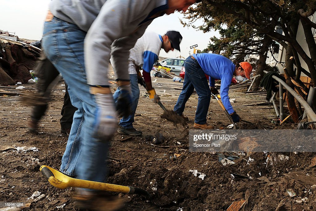 Volunteers help to clean up in the heavily damaged Rockaway neighborhood where a large section of the iconic boardwalk was washed away on November 10...