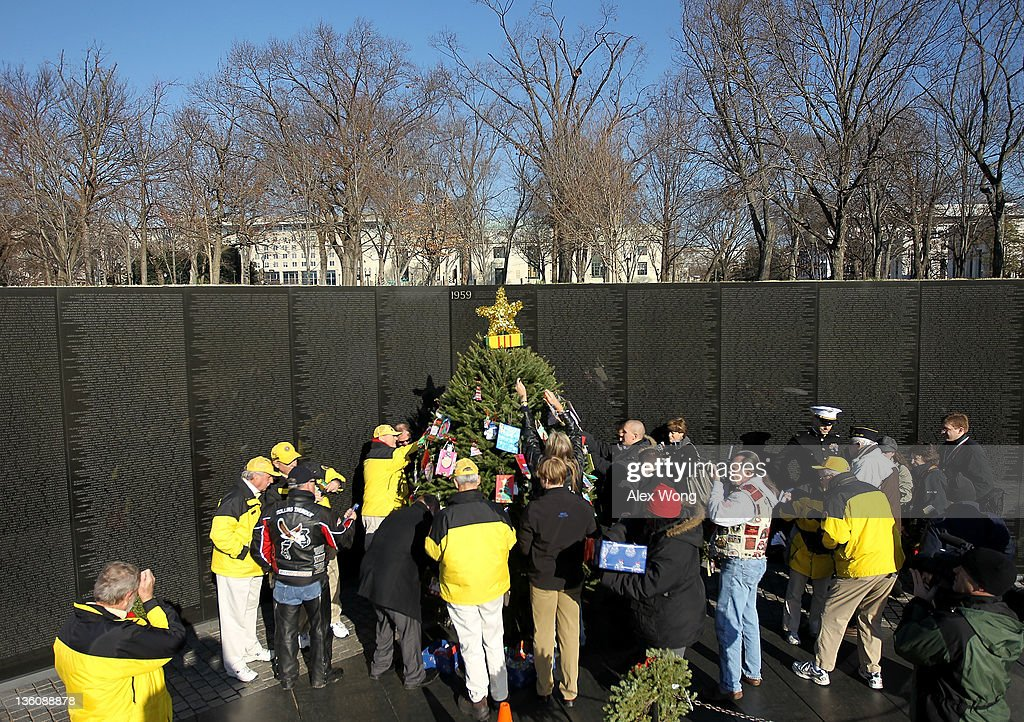 Volunteers help to decorate a Christmas tree at the Vietnam Veterans Memorial December 19, 2011 in Washington, DC. The Vietnam Veterans Memorial Fund (VVMF) honored veterans and active-duty military personnel during its annual Christmas tree ceremony by placing the tree, decorated with homemade holiday greeting cards and ornaments sent by Americans, near the wall of the memorial.