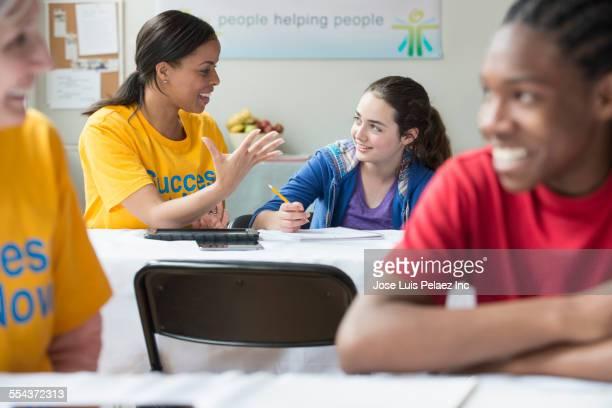 Volunteers helping students in classroom