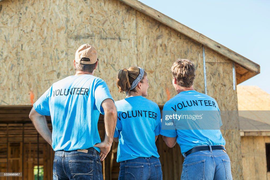 Volunteers helping to build homes for the needy : Stock Photo