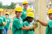Volunteers holding wood frame together