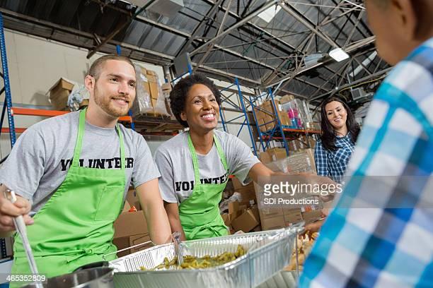 Bénévoles dans la communauté Soupe populaire servant repas chaud pour les familles
