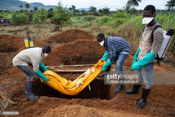 Volunteers in protective suit burry the body of a person who died from Ebola in Waterloo some 30 kilometers southeast of Freetown on October 7 2014...