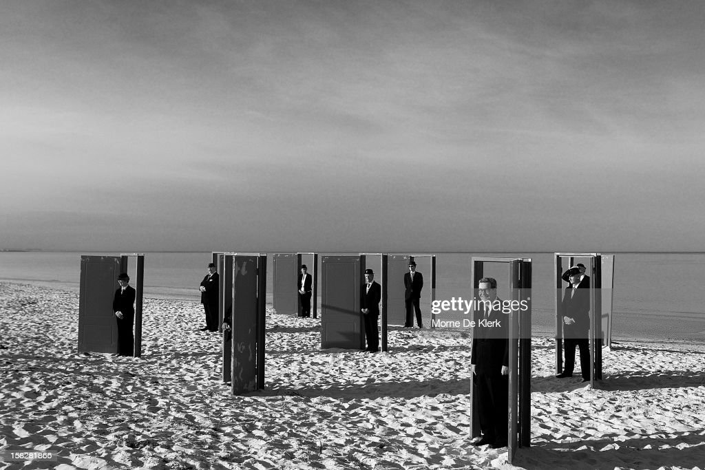 Volunteers including former Australian politician Alexander Downer, pose as they take part in an installation by surrealist artist, Andrew Baines at Henley Beach on December 13, 2012 in Adelaide, Australia. The installation was called 'Doorways To Potential'.