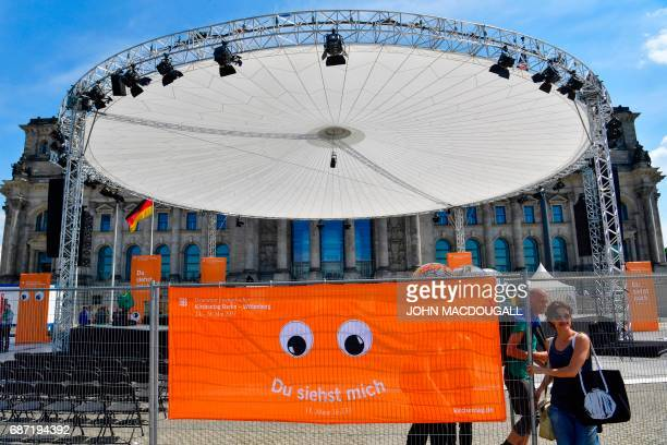 Volunteers leave an enclosed stage area in front of the Reichstag building sealed off ahead of the Kirchentag festival celebrating the 500th...