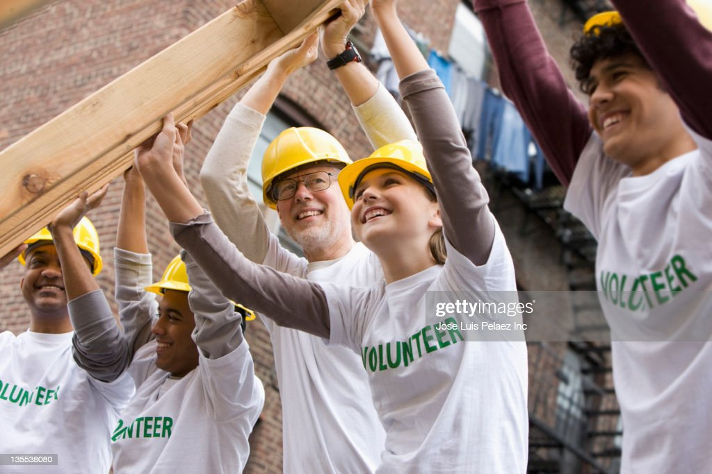 Volunteers lifting construction frame together