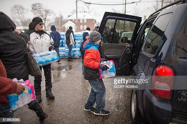 Volunteers load cases of free water into waiting vehicles at a water distribution centre at Salem Lutheran Church in Flint Michigan on March 5 2016...
