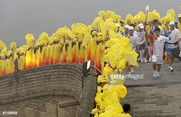Volunteers look on as an Olympic torchbearer takes part in a relay along a section of the Great Wall in Badaling outside Beijing on August 07 2008 a...