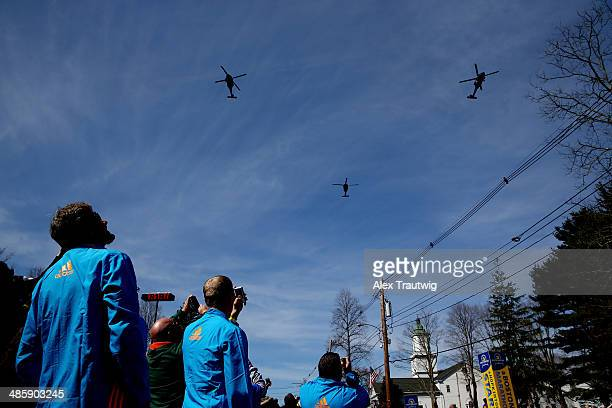 "Volunteers look on during a flyover by the Massachusetts Army National Guard members of ""C"" Company 3rd of the 126th General Support Aviation..."