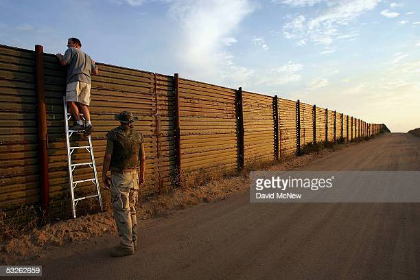 Volunteers look over the USMexico border fence to see how illegal border crossers may jump the fence before going on the nightly patrol by citizen...