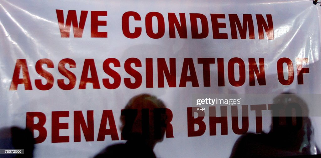 Volunteers of an Indian peace forum stand near a poster condemning the assassination of slain former Pakistani Prime Minister Benazir Bhutto, during a vigil in Mumbai, 29 December 2007. Bhutto was assassinated by a suicide bomber, plunging the nation into one of the worst crises in its history and raising alarm around the world. Violence erupted in cities across Pakistan,Pakistani paramilitary forces in the southern city have been ordered to shoot rioters on sight to prevent unrest after the assassination of former Prime Minister Benazir Bhutto, a paramilitary officer said.AFP PHOTO/Pal PILLAI