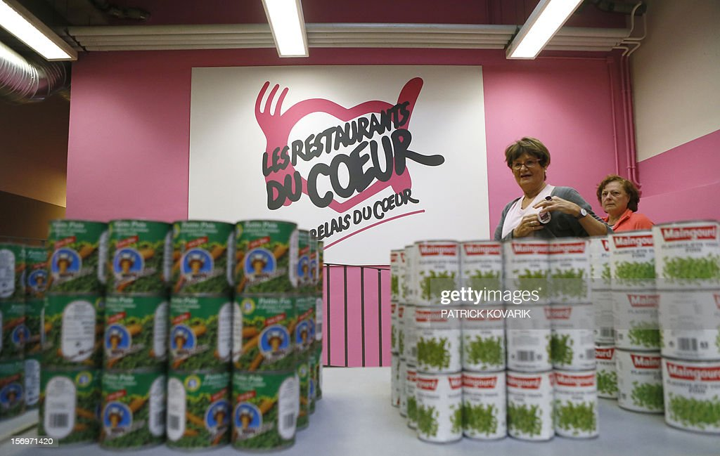 Volunteers of French charitable organisation 'Les Restos du Coeur' (Restaurants of the Heart) stand in front of cans, on November 26, 2012 in Paris, during the launching of the 28th winter campaign to distribute food to the needy.