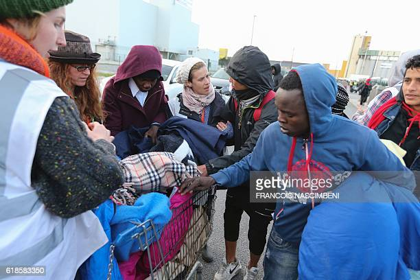 Volunteers of UK registered charity Care4Calais distribute blankets to migrants near the 'Jungle' migrant camp in Calais northern France on October...