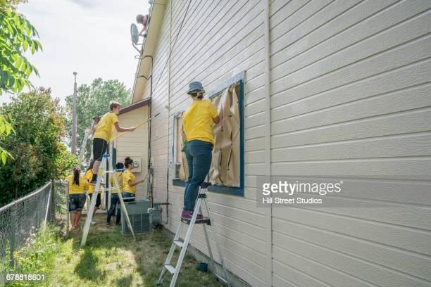 Volunteers on ladders painting house