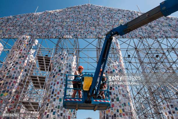 Volunteers operate a mobile lift in order to hang books on the 'Parthenon of Books' by Argentinian artist Marta Minujin at the Documenta 14 art...