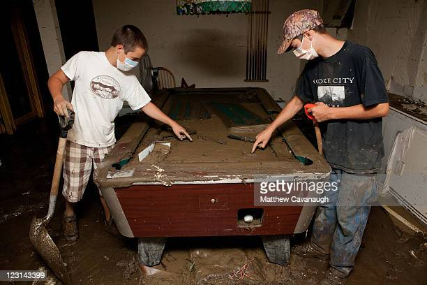 Volunteers Oscar Smith and Hank Sweeney take a break from shoveling debris to write messages on a muddy pool table at The Crafts Inn on West Main...