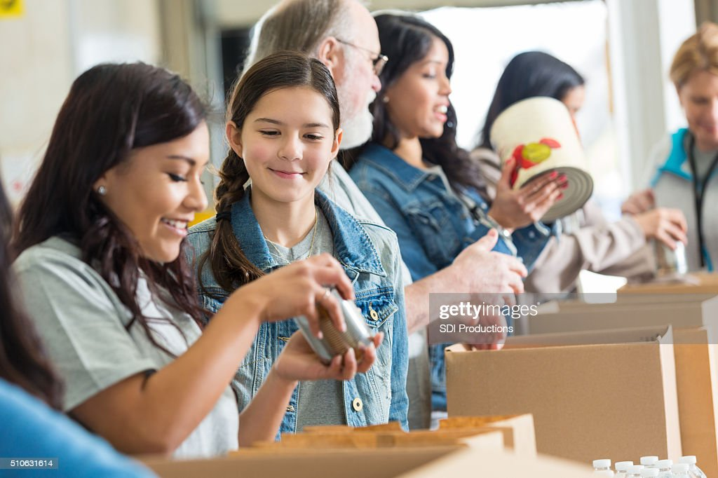 Volunteers pack canned food in community food drive : Stock Photo