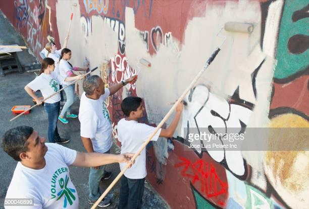 Volunteers painting over graffiti wall