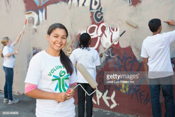 Volunteers painting over graffiti wall