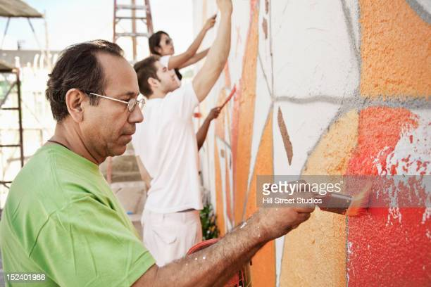 Volunteers painting wall together